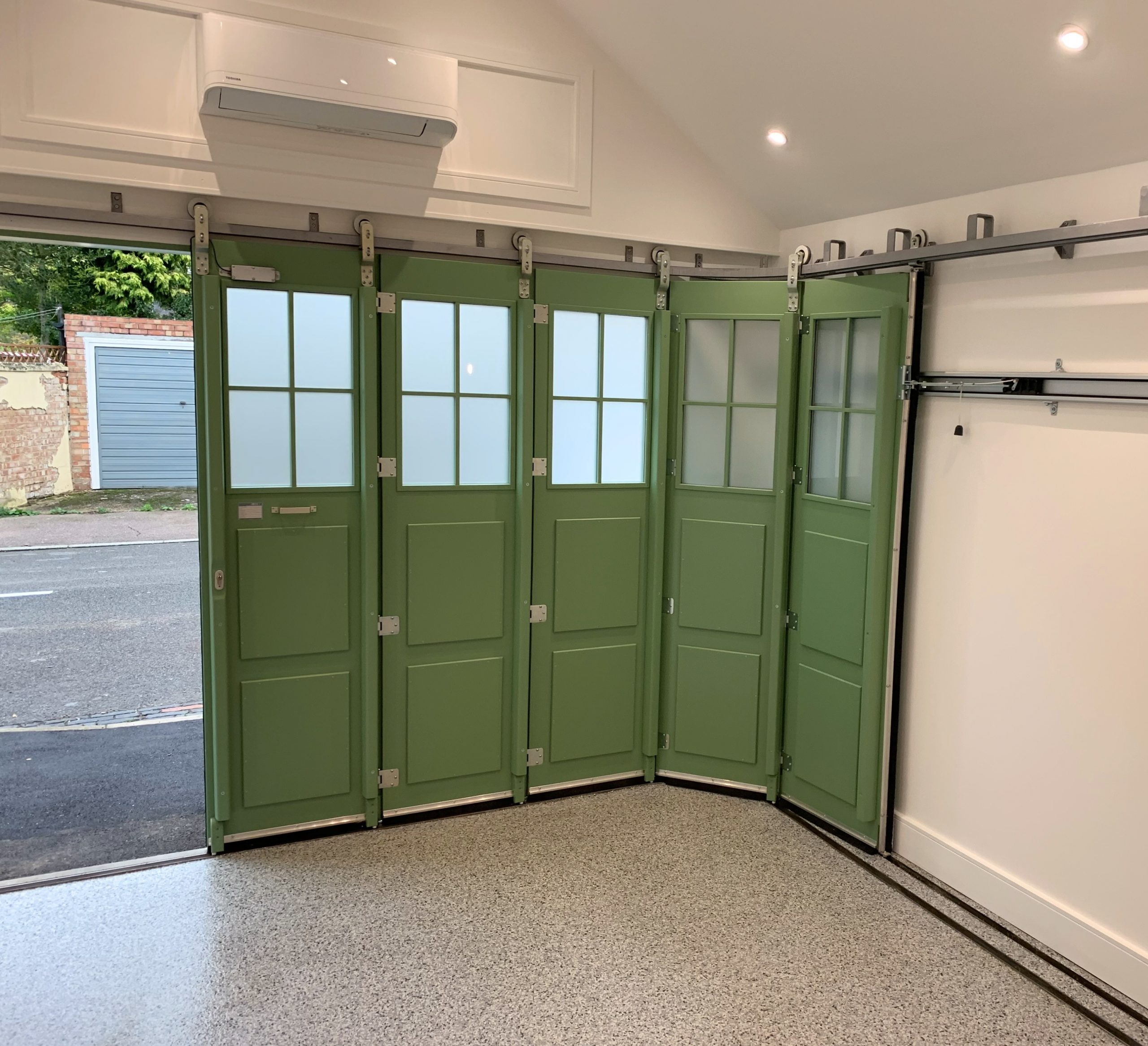 Automated side sliding sectional garage door with glazing