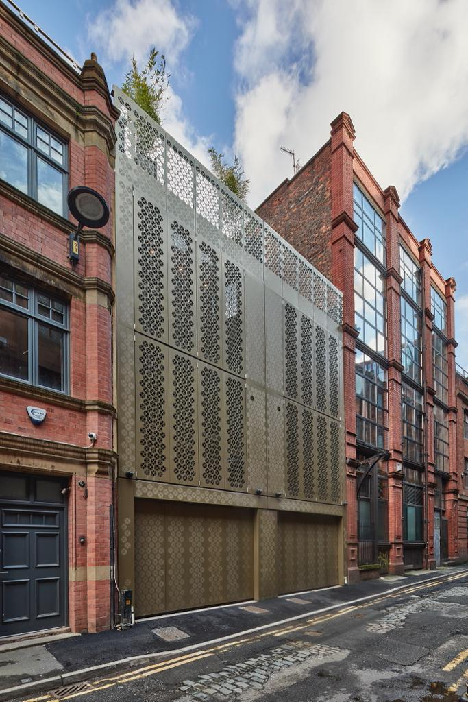 Bronze aluminium sliding sectional garage doors for new townhouses in central Manchester. Copyright Andrew Haslam Photography.